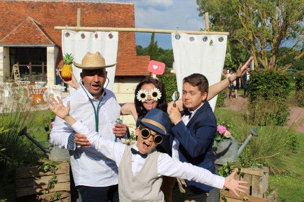 Quatre personnes munies d'accessoires drôles lors d'un mariage en plein air